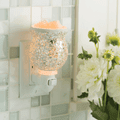 Reflection Glass Pluggable Fragrance Warmer plugged in powerpoint displayed next to flowers and tiled wall in background