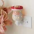 Santa Pluggable Fragrance Warmer plugged into powerpoint and displayed next to flowers