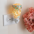 Sea Glass Pluggable Fragrance Warmer plugged in powerpoint displayed next to flowers