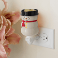 Snowman Pluggable Fragrance Warmer plugged into powerpoint displayed next to flowers
