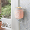 Mason Jar Pluggable Fragrance Warmer plugged into powerpoint in wall near window