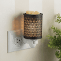 Chevron Metal Pluggable Fragrance Warmer plugged into powerpoint on wall on left side of photo